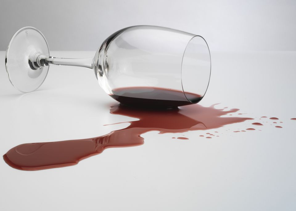 glass of red wine spilled on white tablecloth